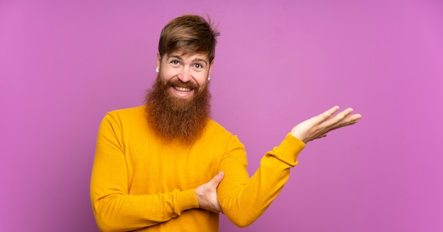 Uomo dai capelli rossi con la barba lunga sopra le mani viola che si estendono lateralmente per invitare a venire