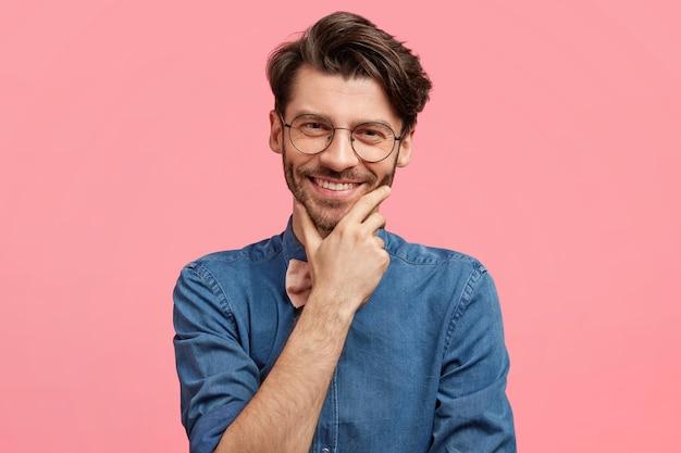 Uomo dai capelli scuri che indossa cravatta a farfalla rosa e camicia di jeans