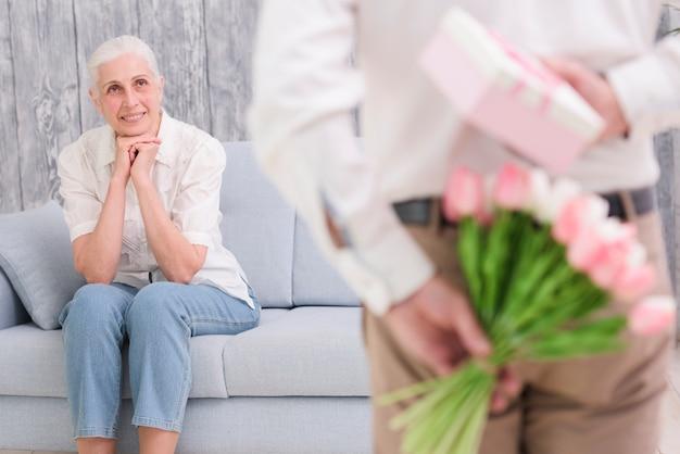 Uomo defocused che nasconde il mazzo e il contenitore di regalo davanti a sua moglie sorridente
