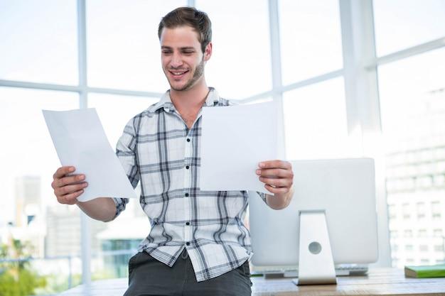 Uomo dei pantaloni a vita bassa che esamina documento in ufficio