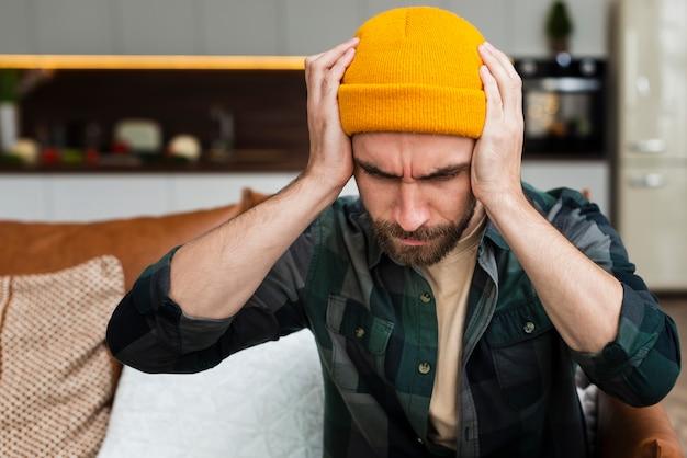 Uomo dei pantaloni a vita bassa che ha mal di testa