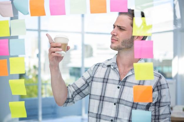 Uomo dei pantaloni a vita bassa che indica al post-it in ufficio