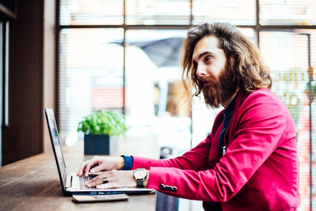 Uomo dei pantaloni a vita bassa che lavora al computer