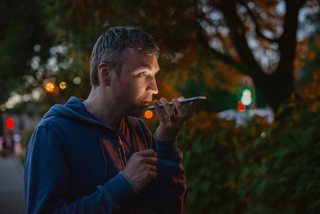Uomo dei pantaloni a vita bassa che parla su un telefono cellulare alla notte nella città