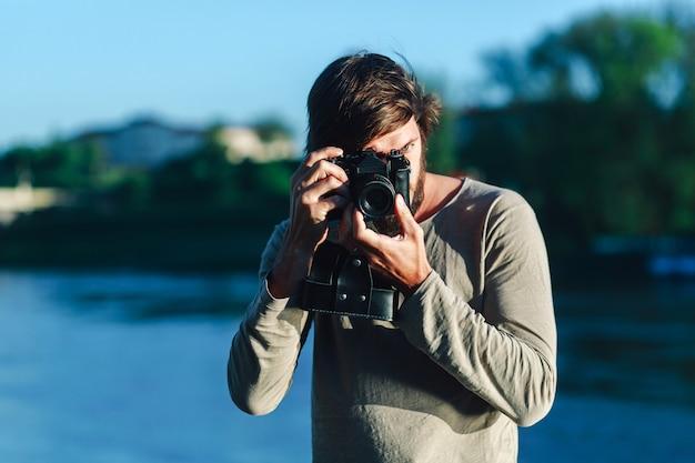 Uomo dei pantaloni a vita bassa che prende una foto sulla retro macchina fotografica all'aperto