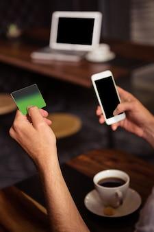 Uomo dei pantaloni a vita bassa che usando la sua carta di credito per comprare online