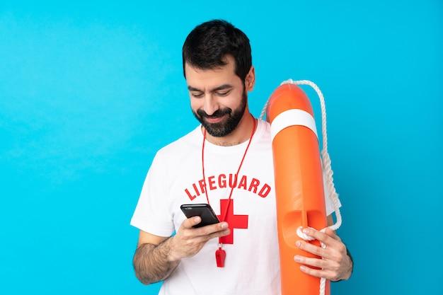 Uomo del bagnino che invia un messaggio con il cellulare