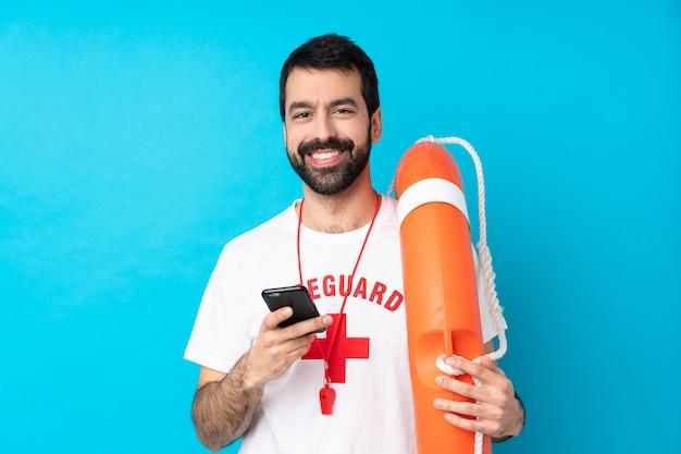 Uomo del bagnino sopra la parete blu isolata che invia un messaggio con il cellulare