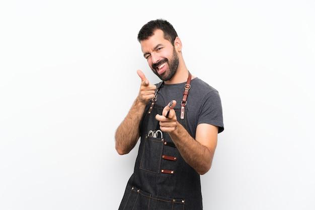 Uomo del barbiere in un grembiule che punta verso la parte anteriore e sorridente
