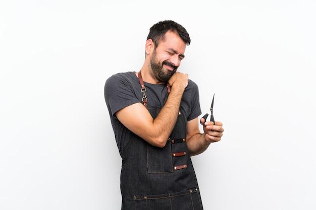Uomo del barbiere in un grembiule che soffre di dolore alla spalla per aver fatto uno sforzo