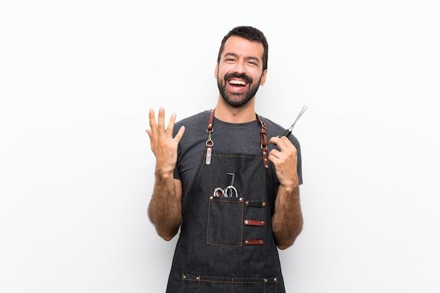 Uomo del barbiere in un grembiule che sorride molto