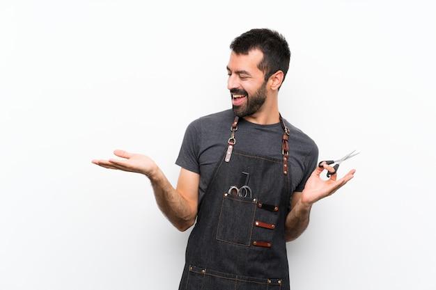 Uomo del barbiere in un grembiule che tiene copyspace con due mani
