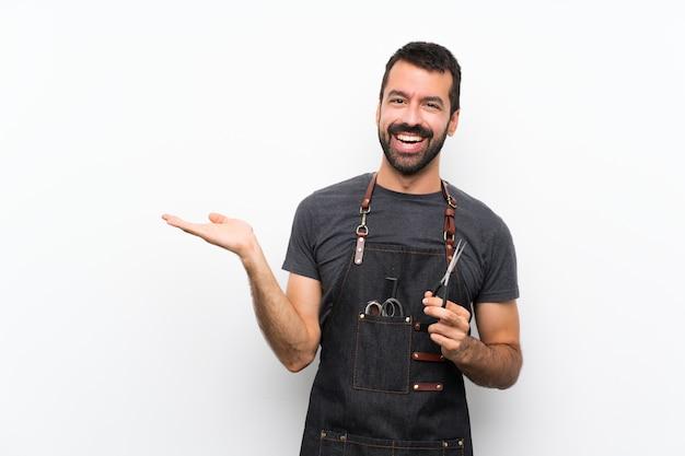 Uomo del barbiere in un grembiule che tiene copyspace immaginario sul palmo per inserire un annuncio