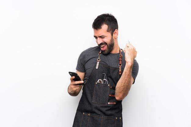 Uomo del barbiere in un grembiule con il telefono in posizione di vittoria