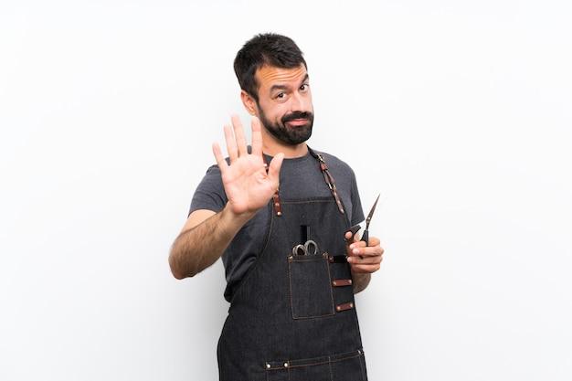 Uomo del barbiere in un grembiule facendo fermata gesto
