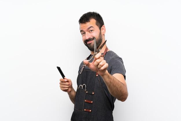 Uomo del barbiere in un grembiule sopra la parete bianca isolata