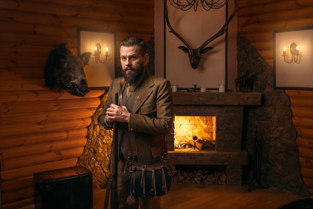Uomo del cacciatore con la vecchia pistola contro il petto antico