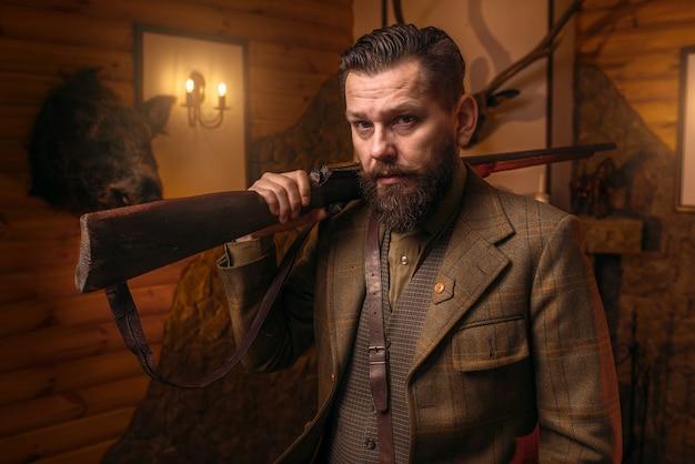 Uomo del cacciatore in abiti vintage con fucile antico