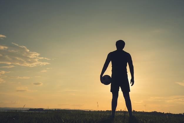 Uomo del calciatore che sta retrovisione in siluetta isolata sul fondo di tramonto
