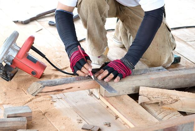 Uomo del carpentiere che misura la plancia di legno per la casa