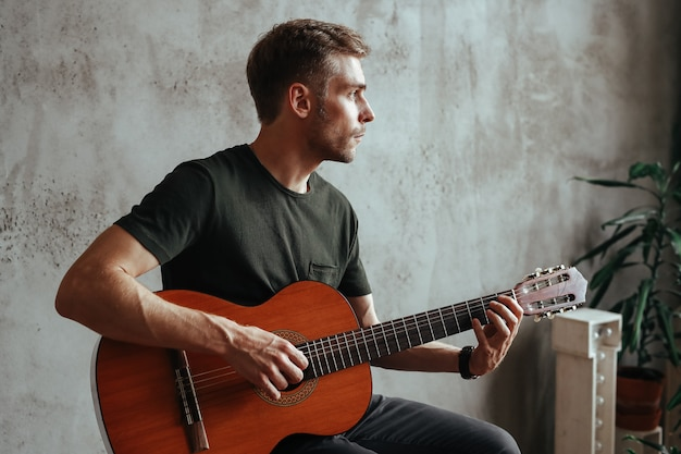 Uomo del chitarrista che gioca chitarra a casa