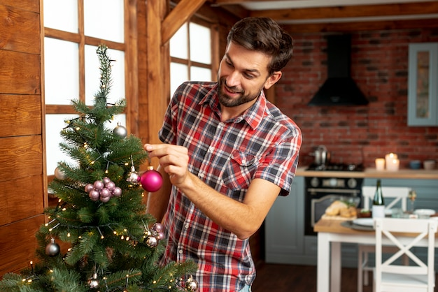 Uomo del colpo medio che decora l'albero di natale