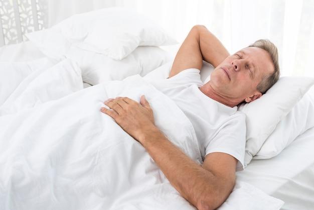 Uomo del colpo medio che dorme con la coperta bianca