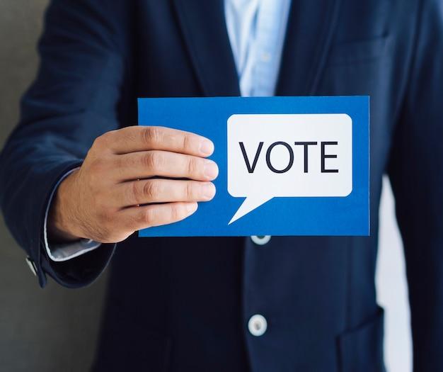 Uomo del colpo medio che mostra una carta di voto con un fumetto