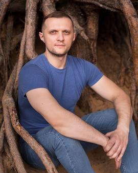 Uomo del colpo medio che posa vicino alle radici degli alberi