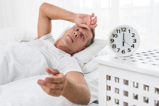 Uomo del colpo medio che sveglia con l'orologio
