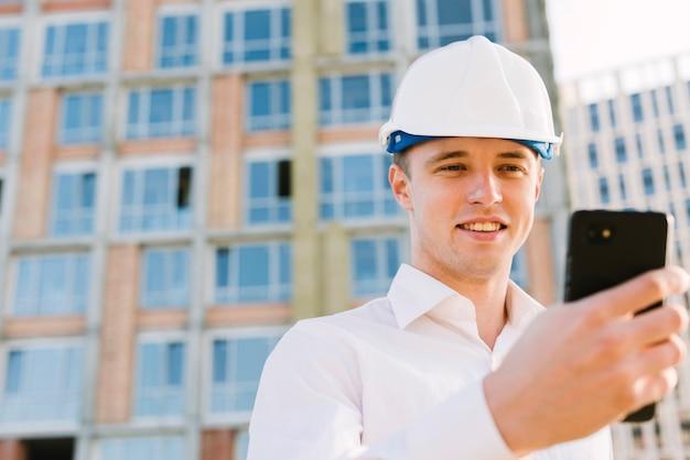 Uomo del colpo medio con il casco che esamina telefono