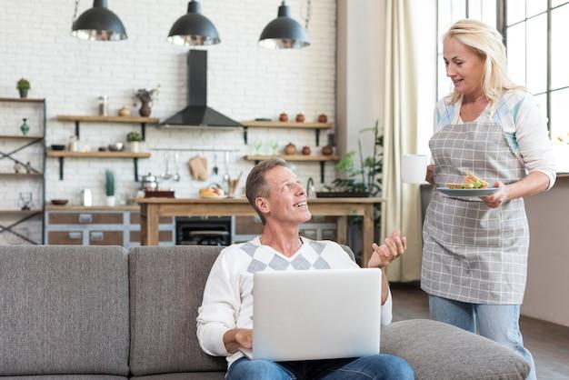 Uomo del colpo medio con il computer portatile che parla con donna