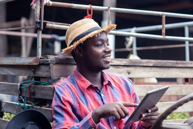 Uomo del coltivatore che per mezzo della compressa con felice e sorridendo sul vecchio trattore