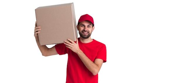 Uomo del corriere che tiene sulla sua spalla una grande scatola di consegna