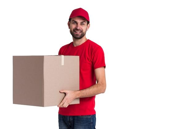 Uomo del corriere che tiene uno spazio della copia della grande scatola di consegna