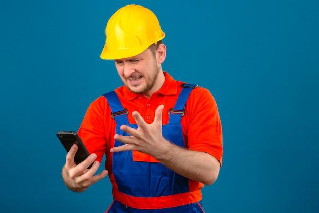 Uomo del costruttore che indossa l'uniforme da costruzione e l'elmetto di sicurezza essendo arrabbiato confuso aggressivo di cattivo umore dopo aver sentito cattive notizie sulla telefonata che urla minaccioso nell'altoparlante del suo smartphone