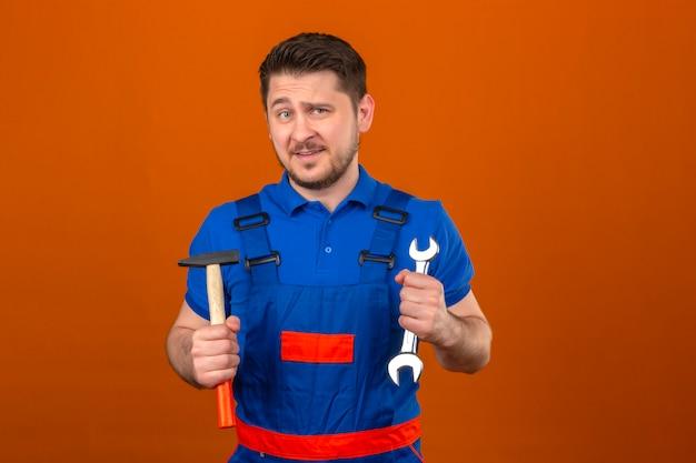 Uomo del costruttore che indossa l'uniforme della costruzione e chiave e martello della tenuta del casco di sicurezza in mani con il sorriso sul fronte che controlla parete arancio isolata