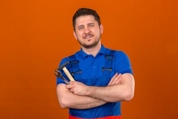 Uomo del costruttore che indossa l'uniforme di costruzione e la chiave di tenuta del casco di sicurezza e il martello nelle mani con il sorriso sul viso guardando fiducioso in piedi sopra la parete arancione isolata
