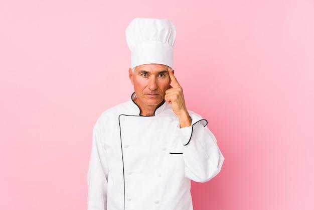 Uomo del cuoco invecchiato centrale isolato tempio indicante con il dito, pensando, focalizzato su un compito.