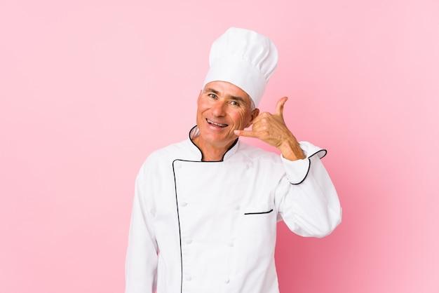 Uomo del cuoco invecchiato mezzo isolato mostrando un gesto di chiamata di telefono cellulare con le dita.