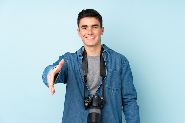 Uomo del fotografo dell'adolescente isolato sull'azzurro