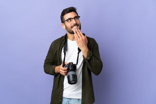Uomo del fotografo sopra la parete viola isolata che osserva in su mentre sorridendo