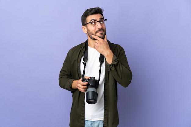 Uomo del fotografo sopra la parete viola isolata che pensa un'idea mentre osservando in su
