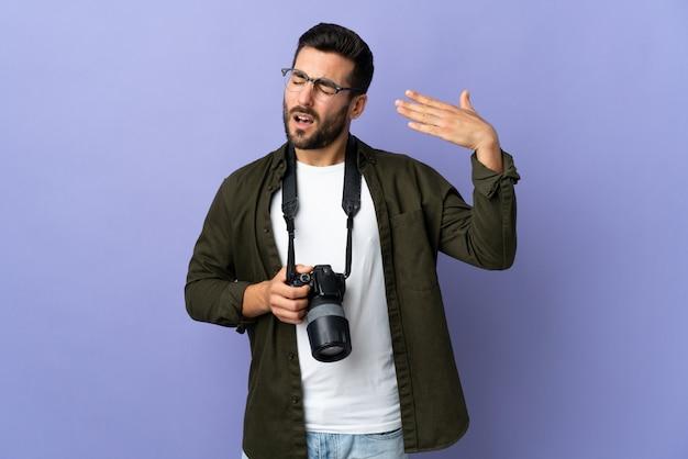 Uomo del fotografo sopra la parete viola isolata con espressione stanca e malata