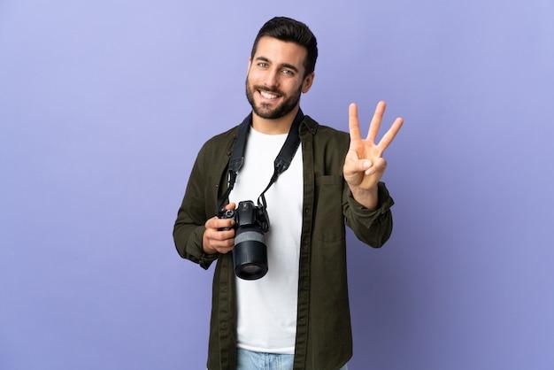 Uomo del fotografo sopra la parete viola isolata felice e contando tre con le dita