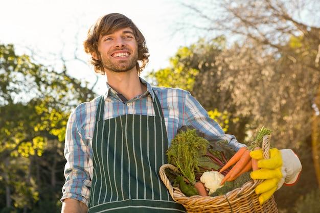 Uomo del giardiniere che tiene un cestino delle verdure nel giardino
