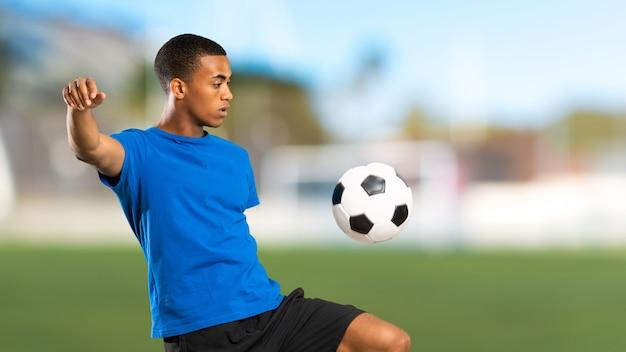 Uomo del giocatore di football americano africano all'aperto