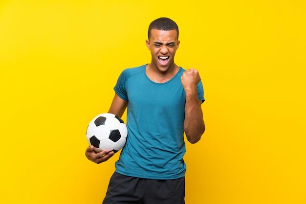 Uomo del giocatore di football americano africano che celebra una vittoria