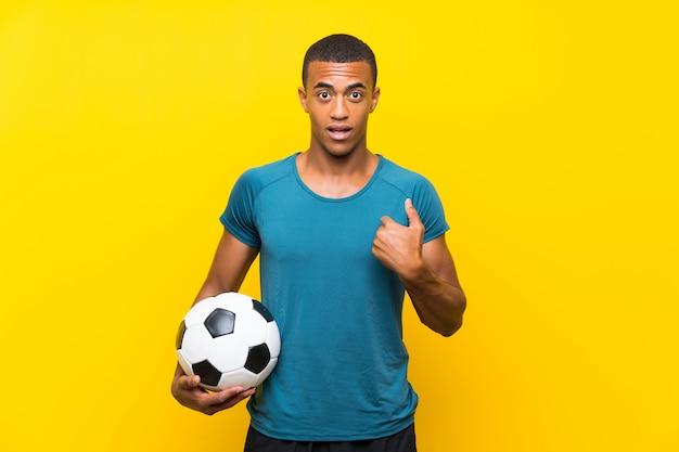 Uomo del giocatore di football americano africano con espressione facciale sorpresa