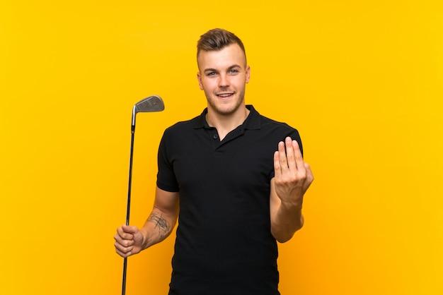 Uomo del giocatore di giocatore di golf sopra fondo giallo isolato che invita a venire con la mano. felice che tu sia venuto